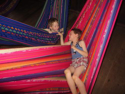 BEST CUYABENO TOURS: Resting in hammocks at the Cofan Lodge when visiting the Amazon in Ecuador.